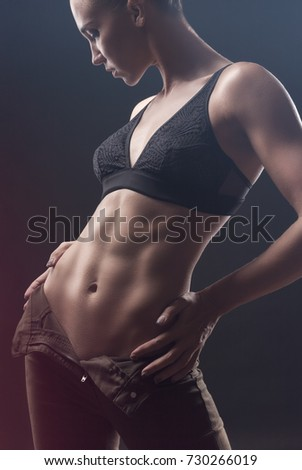 Young sexy woman in jeans and bra against a black background, studio shot