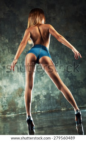 Young sexy woman in jeans chert with naked back standing on wall background. Camera angle view. - stock photo