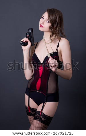 young sexy woman in lingerie posing with gun over grey background - stock photo