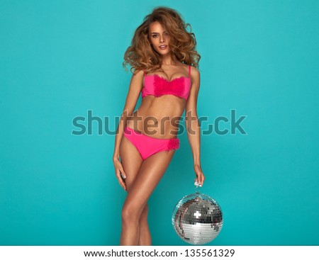 Young sexy woman in pink lingerie keeping disco ball - stock photo