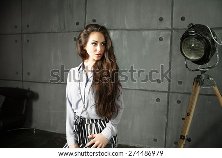 Young sexy woman in rich costume posing  in  studio.Outdoor lifestyle portrait of young business lady in fashion and stylish pantsuit,white shirt and striped pants.Long curly brunette hair - stock photo