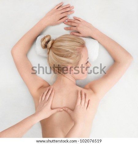 Young sexy woman in spa gets a massage - stock photo