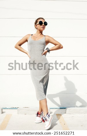 Young sexy woman in sunglasses. Outdoor lifestyle portrait of girl in grey dress - stock photo