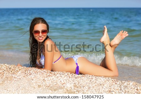 Young sexy woman in swimsuit posing on the beach - stock photo