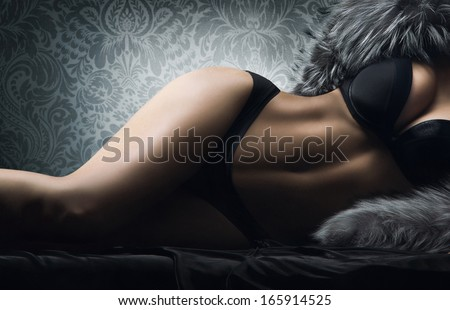 Young sexy woman in vintage lingerie laying in the bed - stock photo