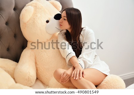 Young sexy woman in white shirt in the bed with big toy plush bear