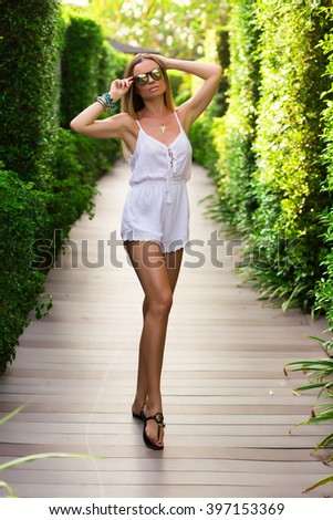 Young sexy woman is posing outside, in tropical garden, sunset, pretty face. - stock photo
