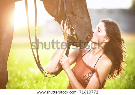 Young sexy woman kiss a horse