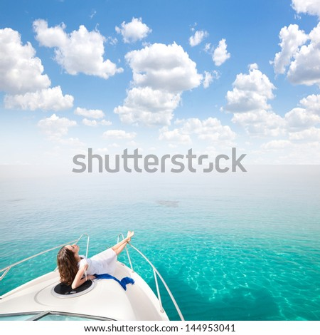 Young sexy woman lies in white dress enjoying clouds in the sky on yacht at the sea - stock photo