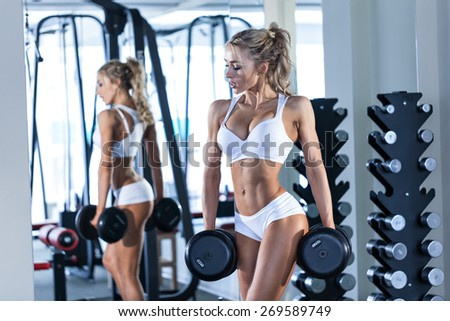 Young sexy woman lifting dumbbells in the gym - stock photo