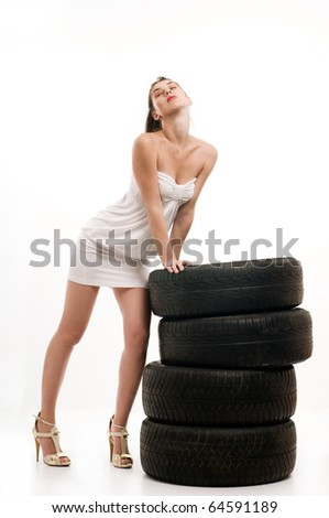 Young sexy woman like vulcaniser with a automobile tire - stock photo