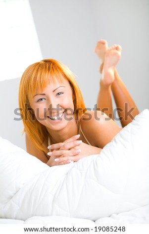 Young sexy woman lying in bed. She's smiling and looking at camera. Front view. - stock photo