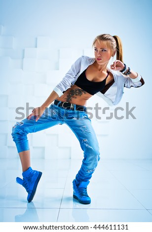 Young sexy woman modern dancer with tattoo on body in bright white interior