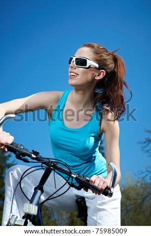 Young sexy woman on a bicykle outdoors smiling