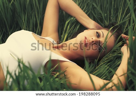 Young sexy woman on grass portrait. - stock photo