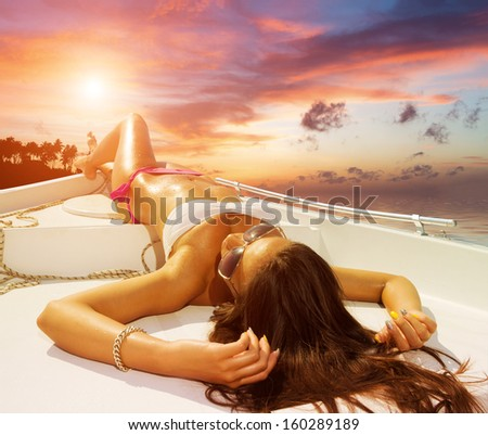 Young sexy woman on her private yacht at sunset - stock photo