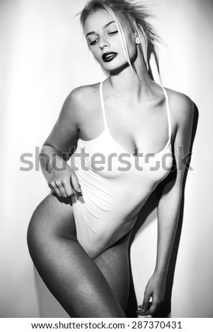 Young sexy woman on wall background. bw - stock photo