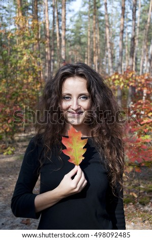 young sexy woman or girl with long brunette curly hair on pretty happy smiling face in autumn seasonal forest or wood holds oak leaves sunny outdoor on natural background
