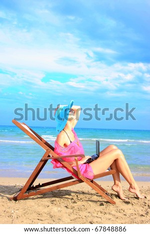 Young sexy woman Relaxing on the beach with her laptop - stock photo