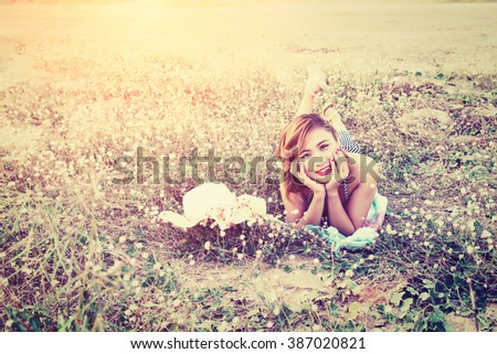 Young sexy woman resting on the flower field. smiling to camera - stock photo