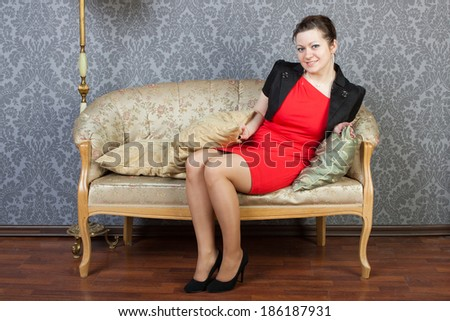young sexy woman sits on a sofa - stock photo