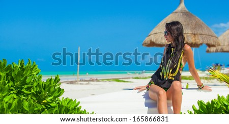 Young sexy woman sitting on a boat in white sandy beach - stock photo