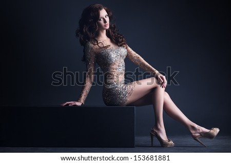 Young sexy woman sitting. On dark background. - stock photo