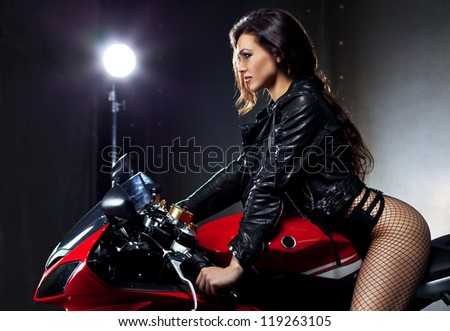 Young sexy woman sitting on motorcycle. - stock photo