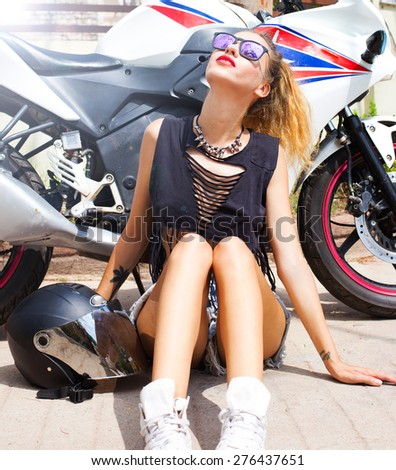 Young sexy woman sitting on the street,with helmet opposite motorbike.Lifestyle portrait bright toned colors,cool rock n roll girl,wear summer outfit,bright summer clothes,denim shorts sunglasses