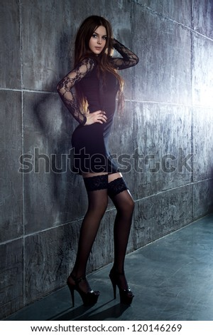 Young sexy woman standing at the wall.