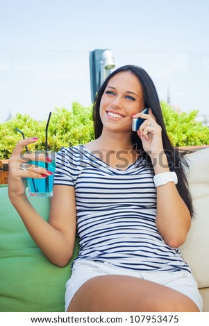 young sexy woman talking on phone in cafe - stock photo