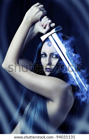 Young sexy woman warrior holding blue fire sword in hands with long healthy black hair. - stock photo