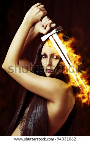 Young sexy woman warrior holding fire sword in hands with long healthy black hair. - stock photo