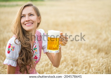 Young sexy woman wearing a dirndl with beer mug over wheat field. soft daylight - stock photo