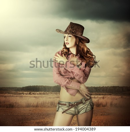 Young sexy Woman wearing cowboy hat and sexy shorts outdoor - stock photo