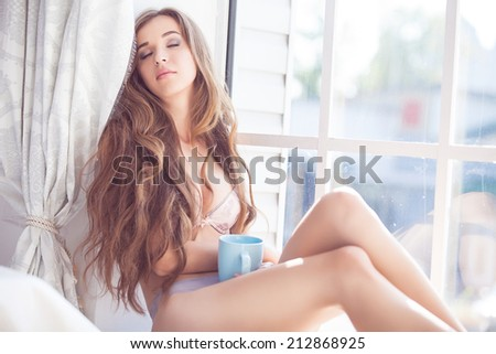 Young sexy woman wearing lingerie. Young woman enjoying her morning coffee. - stock photo