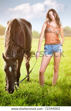 Young sexy woman with a horse - stock photo
