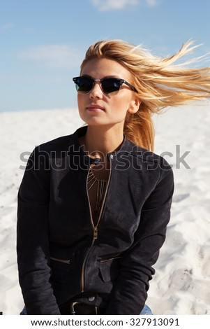 Young sexy woman with blonde hair posing on the white sand in sunny day. Wearing suede jacket, mirrored sunglasses. Lifestyle fashion portrait bright toned colors. The wind blew her hair - stock photo