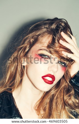 Young sexy woman with bright art makeup on pretty face and beautiful long hair on grey background