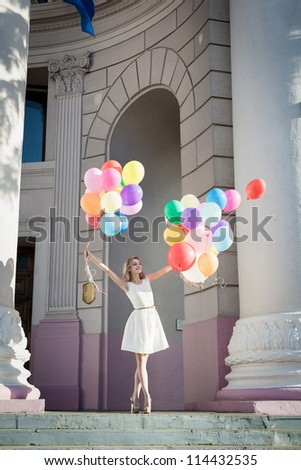 Young sexy woman with colorful latex balloons keeping her dress, urban scene, outdoors - stock photo