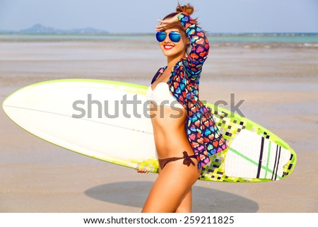 Young sexy woman with ginger hairs, red lips and sportive tanned body  posing with surf board near blue ocean in sunny summer day, ready for surfing. Positive emotions, bright colors. - stock photo