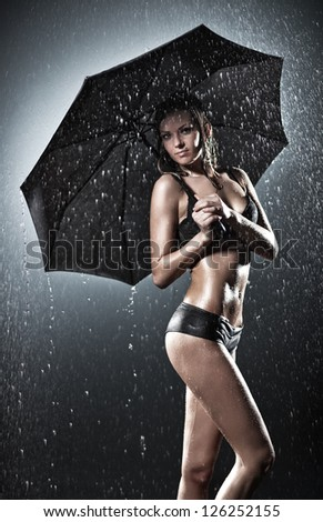 Young sexy woman with umbrella. Water studio photo. - stock photo