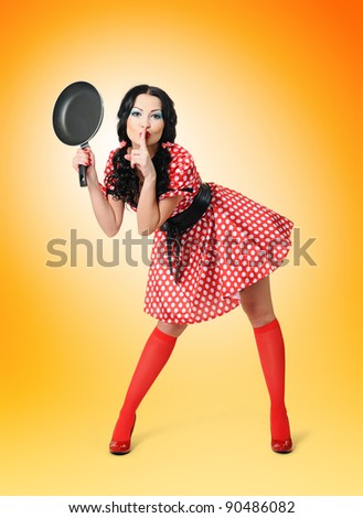 Young sexy womanl in a polka dot dress with frying pan on yellow background, pinup concept - stock photo