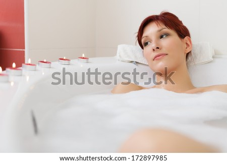Young sexy women relaxing in a bathtube, with candles all over bathtub  - stock photo
