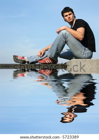 Young sexy young man sitting on the stone blocks with reflection - stock photo