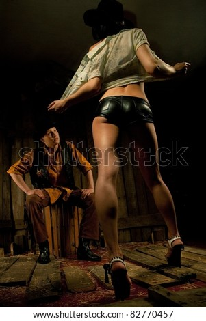 Young sheriff looking at woman taking off her clothes against wooden background - stock photo