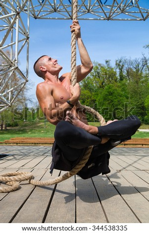 Young shirtless athlete man sitting on the plank floor climbing the rope.