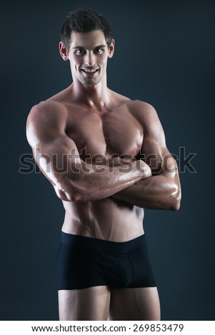 Young shirtless body builder with great smile in shorts - stock photo