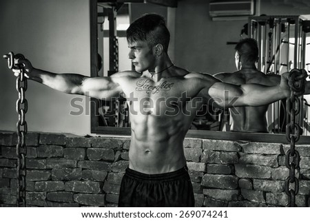 Young shirtless male bodybuilder in gym posing with metal chains in his hands, arms spread open - stock photo