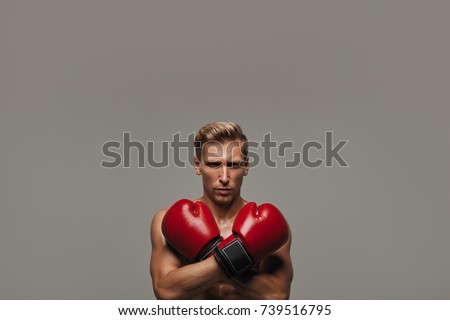 Young shirtless man posing with hands crossed wearing red boxing gloves looking at camera.